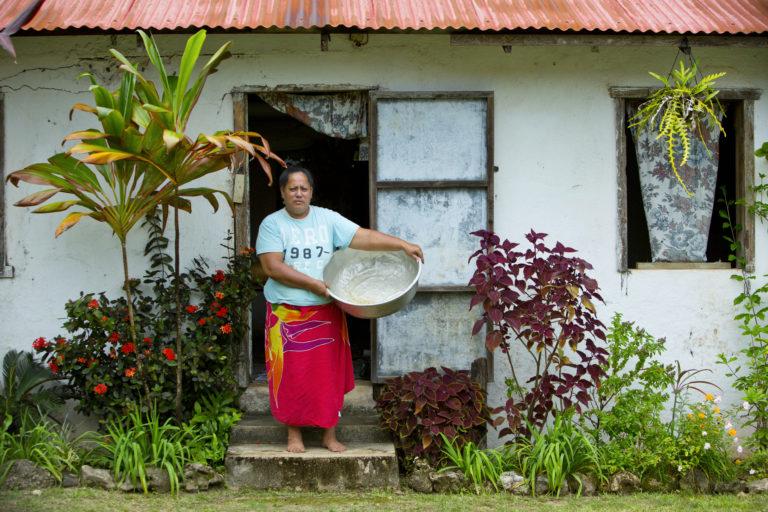 habitant de l'ile portant une bassine devant sa maison
